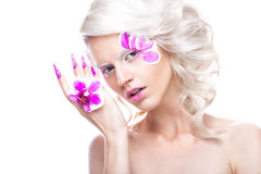 Beautiful girl with art make-up, flowers, curls and long nails. Manicure design. The beauty of the face. Royalty Free Stock Image