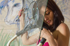 Beautiful girl art with a painted dream catcher. Beautiful girl artist paints on glass figure stock photos