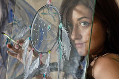 Beautiful girl art with a painted dream catcher. Beautiful girl artist paints on glass figure royalty free stock photos