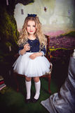 Beautiful girl as Alice in Wonderland. Beautiful girl in the image of Alice in Wonderland with a glass bottle in her hand Stock Photos