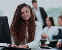 Beautiful girl assistant in the office in front of a computer in. Close up of a girl clerk in the workplace in front of a computer .photo on the background of Royalty Free Stock Photos