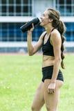 Beautiful girl athlete drinking water Stock Photography