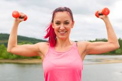 Beautiful girl athlete poses exercising with small weights dumbbell in outdoors.  stock image