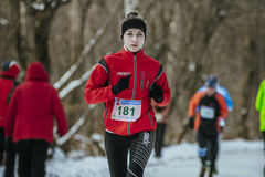 Beautiful girl athlete running down alley winter Park Stock Image