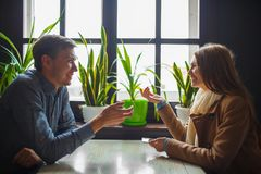 Beautiful girl and attractive man talking in the cafe. royalty free stock images