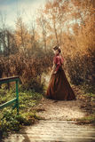 Beautiful girl in the autumn forest. Beautiful girl in a historical dress is walking in the autumn forest Stock Images