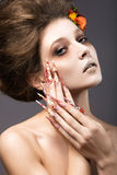 Beautiful girl in autumn image with long nails with bright and unusual make-up. Stock Photo