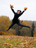 Beautiful girl with autumn leafs in a park jumping Royalty Free Stock Photography