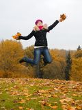 Beautiful girl with autumn leafs in a park jumping Royalty Free Stock Images