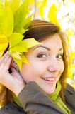 Beautiful girl with autumn leaves. Young beautiful european girl with bunch of autumn yellow leaves royalty free stock photography