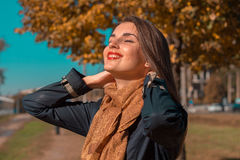 Beautiful girl in autumn Park keeps hands behind the neck closed her eyes and smiles Royalty Free Stock Images