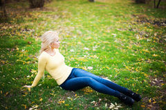 Beautiful girl in the autumn park sitting on. The grass Stock Photo