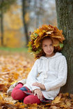 Beautiful girl in autumn park with wreath of Royalty Free Stock Photo
