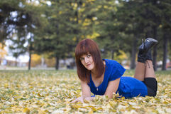 Beautiful girl in autumn. Pretty girl lies on yellow leaves in the park while walking Stock Photography