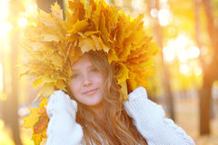 Beautiful girl in the autumn wreath of yellow leaves.  Stock Photo