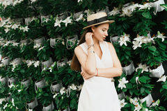 Beautiful girl on the background of flowers. Beautiful girl in a hat on a color background Royalty Free Stock Images