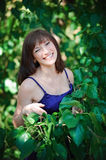 Beautiful girl on a background of green leaves in summer park Royalty Free Stock Photography