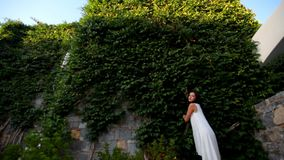 Beautiful girl on the background of a high stone wall with ivy. Beautiful brunette girl in white dress stands on a high hedgehog background of ivy. Greece stock video