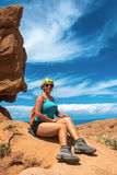 The beautiful girl on a background of orange rocks and blue sky. Royalty Free Stock Photo