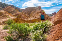 The beautiful girl on a background of orange rocks and green bus Royalty Free Stock Image