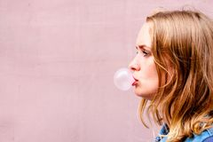 A beautiful girl on an background of a pink tint stands in profile and puffs a ball of chewing gum. stock image