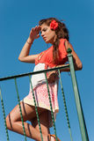Beautiful girl at balcony with fashion dress and hair flower Royalty Free Stock Photo