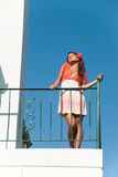 Beautiful girl at balcony with fashion dress and hair flower Stock Photos