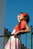 Beautiful girl at balcony with fashion dress and hair flower Royalty Free Stock Image