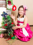 Beautiful girl in ball dress by fireplace. Christmas Royalty Free Stock Image