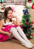 Beautiful girl in ball dress by fireplace. Christmas Stock Images