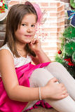 Beautiful girl in ball dress by fireplace. Christmas Royalty Free Stock Photography