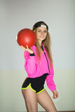 Beautiful girl with a ball. Beautiful slender girl in a sport suit with a ball in her hand Royalty Free Stock Images