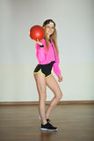Beautiful girl with a ball. Beautiful slender girl in a sport suit with a ball in her hand Royalty Free Stock Photo
