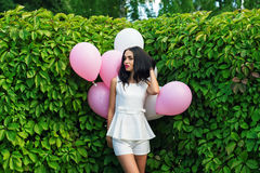 Beautiful girl with balloons in green hedgerow Stock Photo
