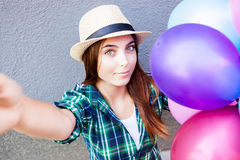 Beautiful girl with balloons make selfie photo. Beautiful teenage girl with air balloons make selfie photo Stock Images