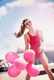 Beautiful girl with balloons on the roof Stock Photos