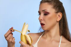 Beautiful girl with banana in studio, isolated. Food, fashion, healthcare, cosmetics concept, space for text
