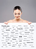 Beautiful girl with a banner of world's different languages Stock Photo