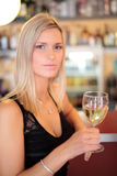 Beautiful girl in a bar, drinking. Beautiful woman standing in a bar, drinking wine. Shallow depth of field, focus is on the eyes royalty free stock photos
