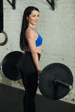 Beautiful girl with a barbell. Beautiful young girl with an excellent figure with a barbell in hand with a smile on her face in the gym Royalty Free Stock Photos