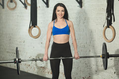 Beautiful girl with a barbell. Beautiful young girl with an excellent figure with a barbell in her arms in the gym Royalty Free Stock Photography