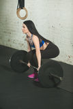 Beautiful girl with a barbell. Beautiful young girl with a barbell in a squat in a perfect figure Royalty Free Stock Photo