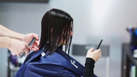 Beautiful girl in a barber shop. The client beauty sitting before a mirror a blue dress and holding a mobile phone. stock video