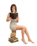 Beautiful girl with a book sitting on a pile of books Stock Photo