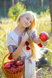 Beautiful girl with a basket of apples. Beautiful girl offering an apple Royalty Free Stock Photo