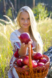 Beautiful girl with a basket of apples. Beautiful girl offering an apple Royalty Free Stock Images