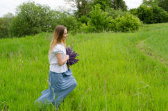 Beautiful girl with basket of flowers is running along field Royalty Free Stock Photos