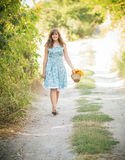 Beautiful girl with a basket of flowers on a walk Stock Image