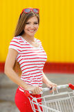 Beautiful girl with a basket in a large supermarket Royalty Free Stock Photos