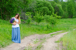 Beautiful girl with basket of meadow flowers on rural road Royalty Free Stock Photography